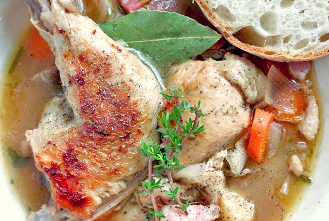 Coq au vin auf Teller mit Brot